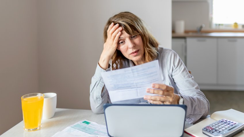 Stressed and Worried Senior Woman Calculating Domestic Expenses, Sitting at Dining Table in Front of Open Laptop Computer.