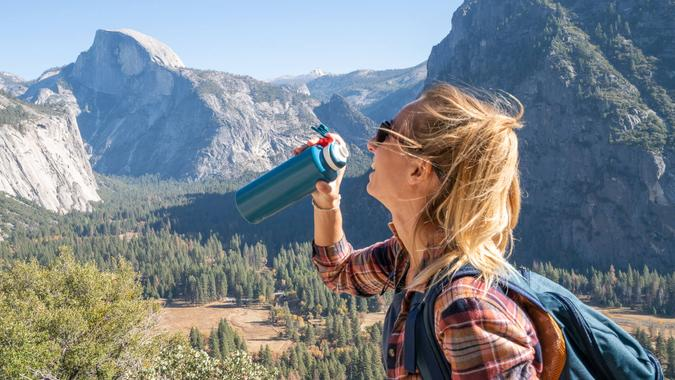 Young woman on top of Yosemite valley, USA drinking water from reusable bottle.