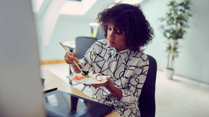 African businesswoman eating sushi at her desk in the office.