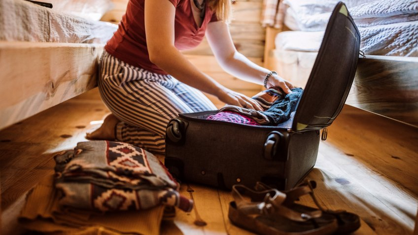 Unrecognizable woman packing luggage in log cabin, sitting on floor.