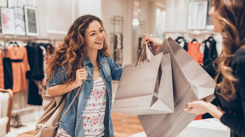 Young woman taking her shopping bags in a fashion store.