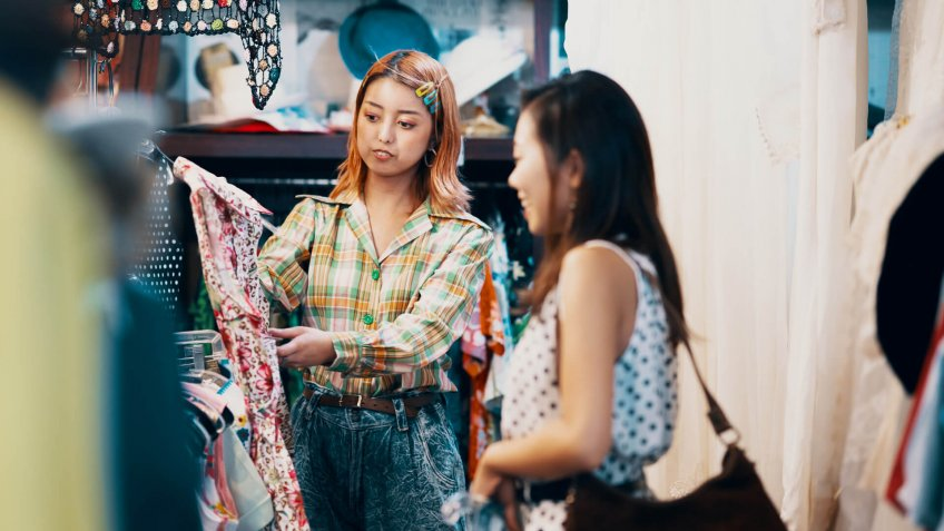 Sales clerk assisting a customer in a thrift store in Japan.