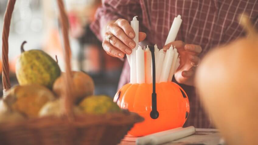 Selecting and placing candles for Halloween decorations.