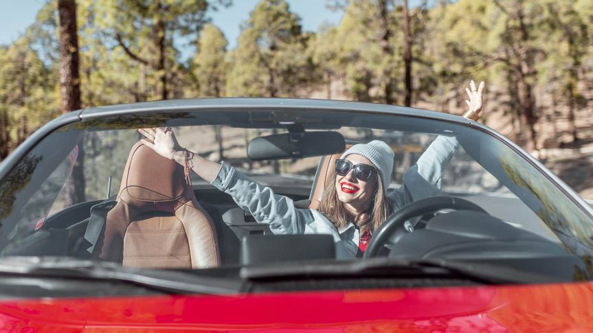 Portrait of a woman driving convertible car while traveling on the forest road, view through the windshield.
