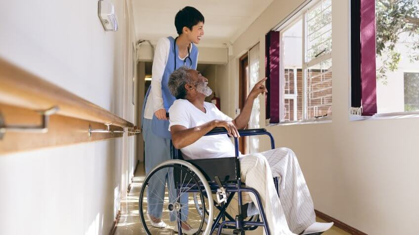 Side view of Asian female nurse and senior African-american male patient interacting with each other while standing in corridor at retirement home.