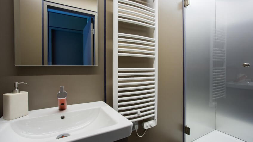 Fragment of the bathroom interior with sink and towel rail on the wall.