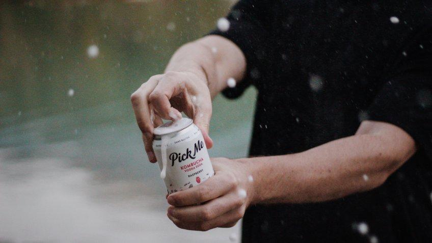 man opens kombucha vodka soda can.