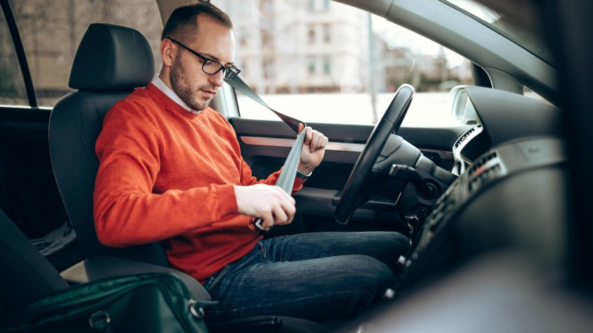 Photo of young man pulling seat belt in the car.