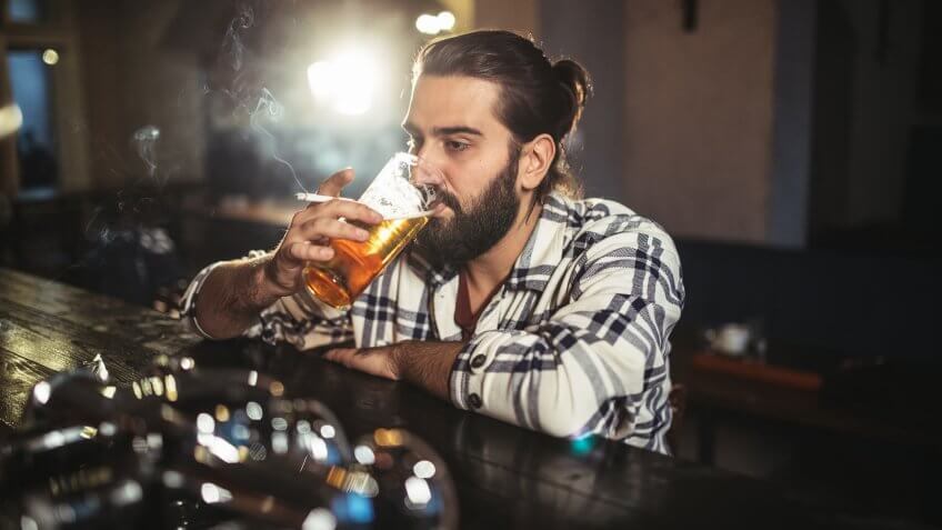 One man, sitting at the bar counter alone, he has drinking problems.
