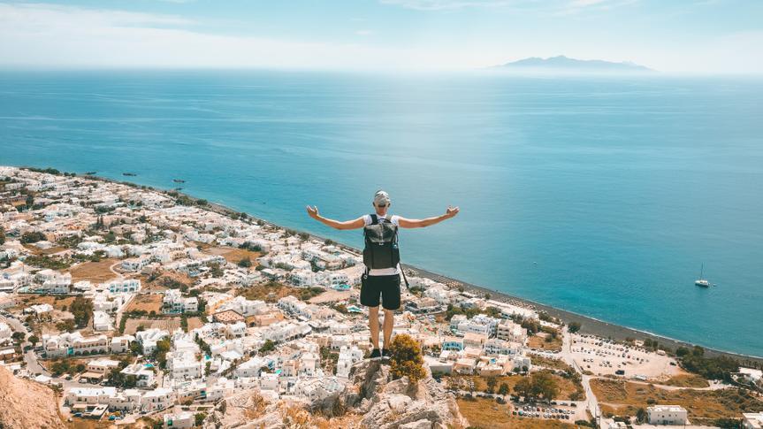 Man sitting on the rock and looking down on Kamari village with the beach in Santorini island, Greece.