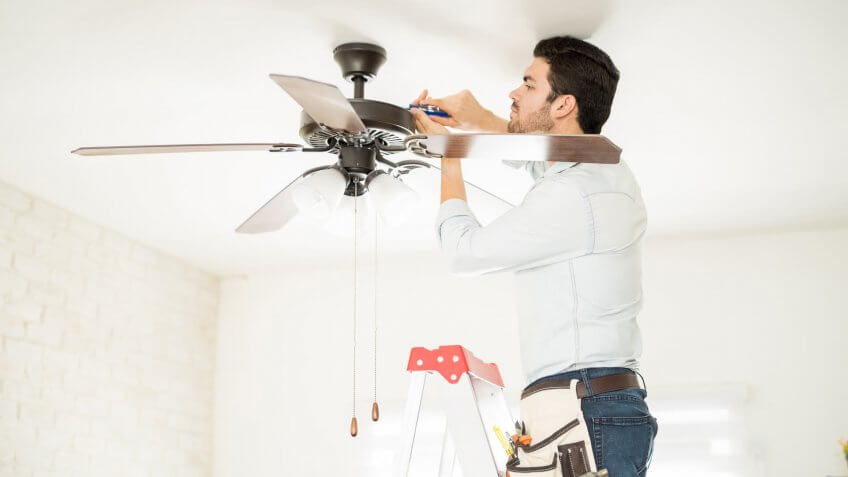 Attractive young handyman stepping on a ladder and fixing a ceiling fan.