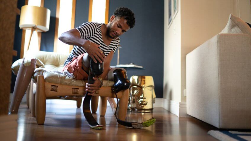 Young man putting prosthetic leg at home.