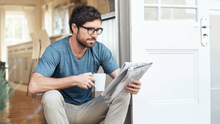 Cropped shot of a handsome young man enjoying his coffee while reading the morning paper.