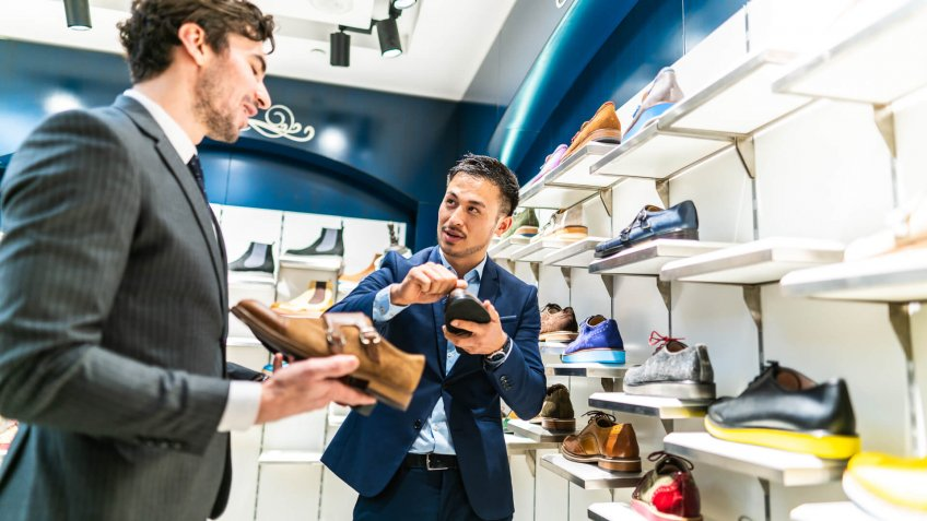 Chinese seller man showing to young handsome businessman in suit leather shoes in shopping store.