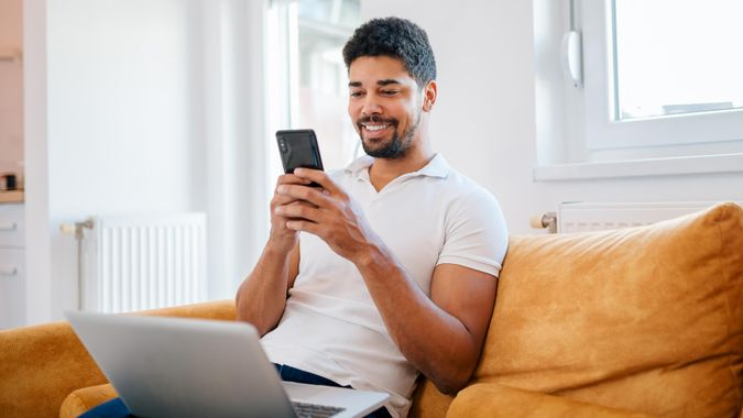 Smiling casual mixed-race freelancer using smart phone and laptop while sitting on the sofa.