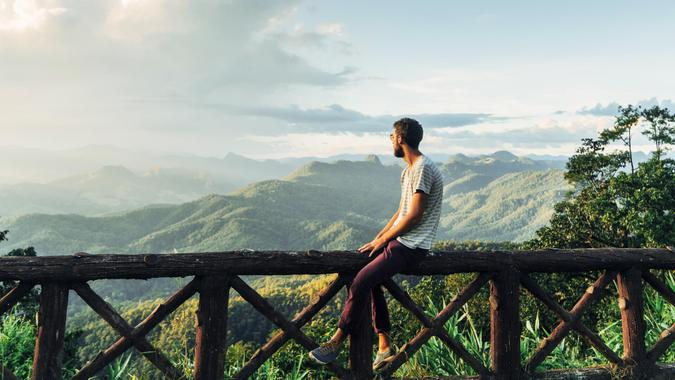 Man on the background of beautiful sunset over green mountain hills in North of Thailand.