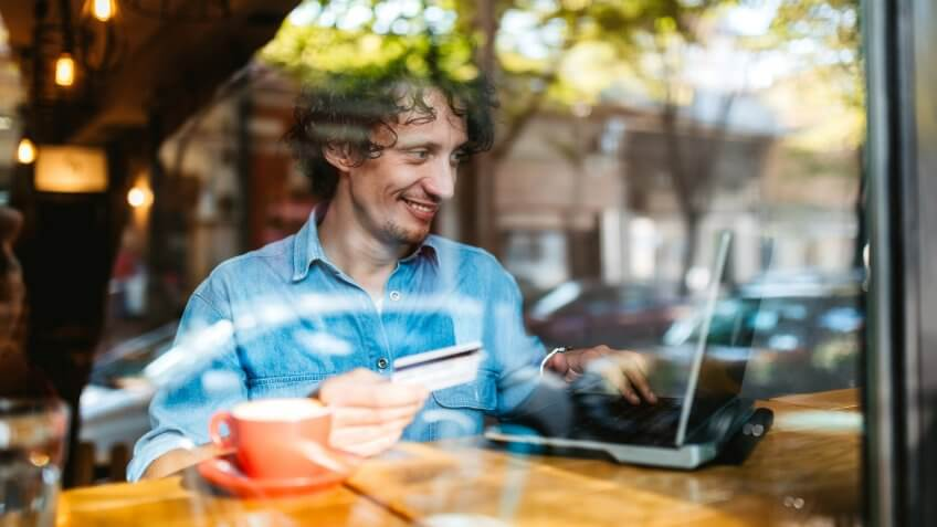 Young handsome Caucasian man using credit card for online on laptop at a cafe.