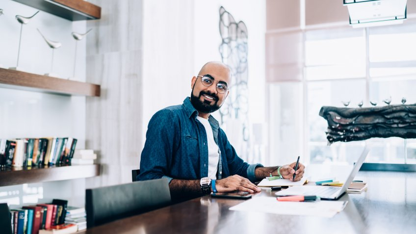 Cheerful handsome ethnic man with beard sitting with laptop and notepad at table in trendy office smiling away to colleague.