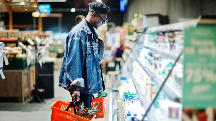 Stylish casual african american man at jeans jacket and black beret holding two baskets, standing near fridge and shopping at supermarket.
