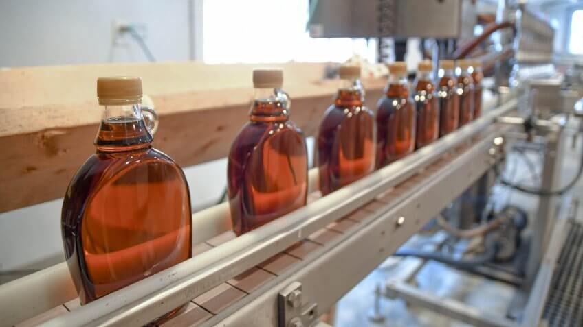 Bottles of maple syrup line a rack in a small syrup production facility on a farm in New Hampshire, USA.