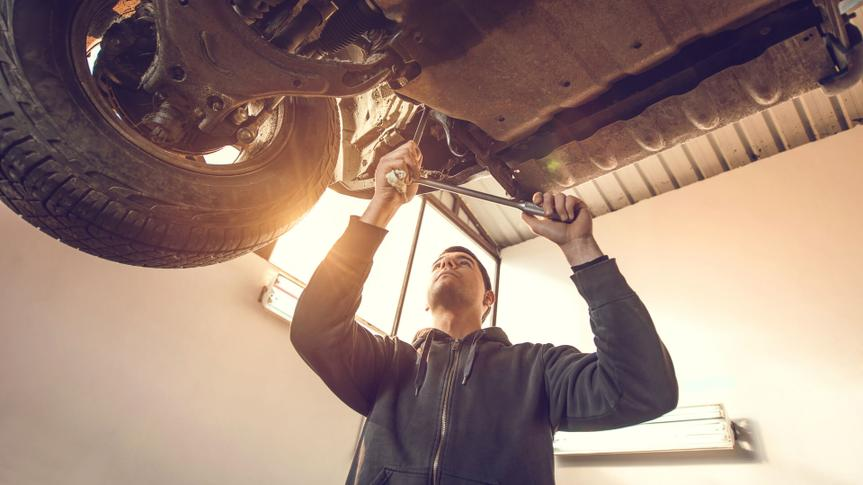 Low angle view of auto mechanic working on a chassis of a car in auto repair shop.