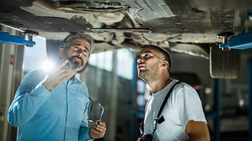 Mid adult customer and auto repairman analyzing chassis in a workshop.