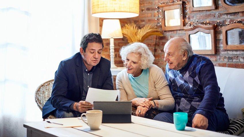 Financial advisor explaining senior couple at home.