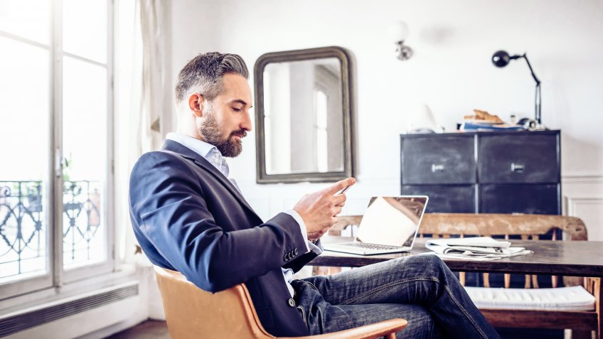 bearded business man reading on mobile in home office.