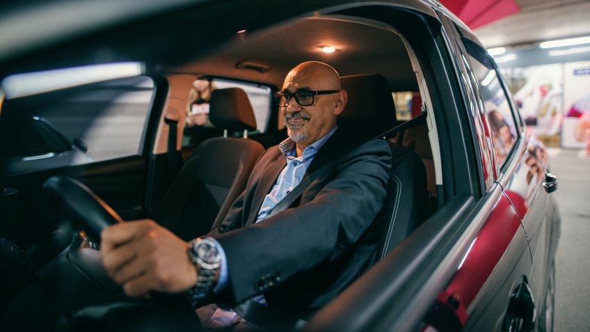 Smiling bearded senior adult driving car at night.