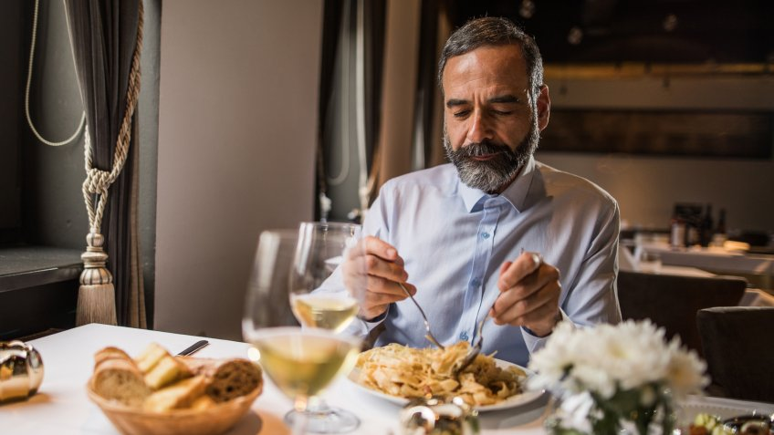 Mature man sitting in a restaurant and eating pasta for lunch.