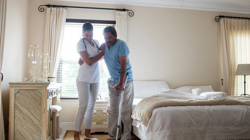 Female doctor helping senior man to walk with crutches in bedroom at home.