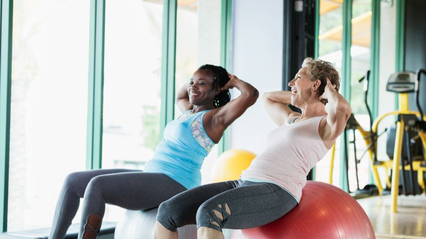 Two multi-ethnic women exercising together at the gym, sitting side by side on giant medicine balls, hands behind their heads.