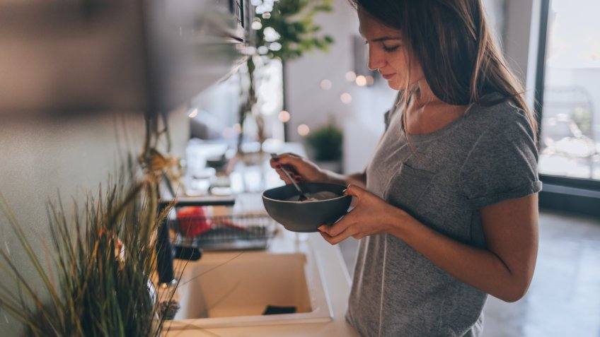 Young woman having healthy breakfast in the morning in her apartment.