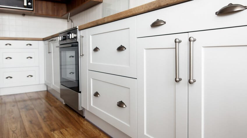 Stylish light gray handles on cabinets close-up, kitchen interior with modern furniture and stainless steel appliances.