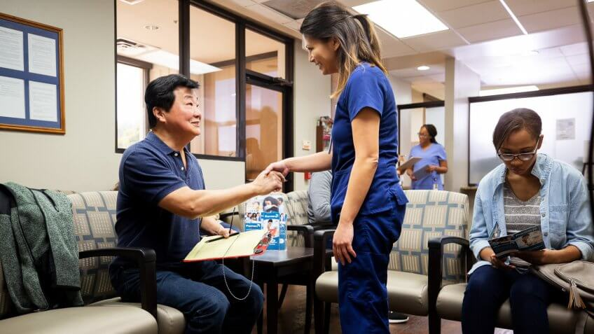 A mid adult female nurse shakes hands with the mature adult male patient in the busy waiting room.