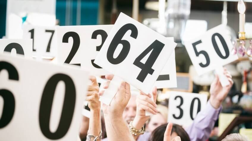 A crowd of bidders at an auction, holding their numbered bidding paddles in the air.