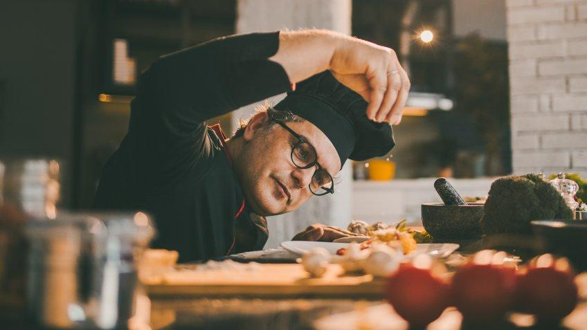 experienced chef adding spices to the meal he is preparing