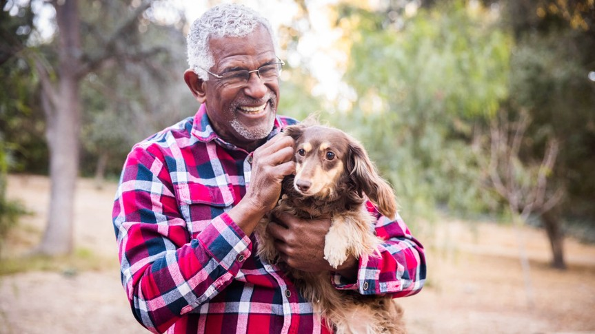 An African American senior man playing with his dog.