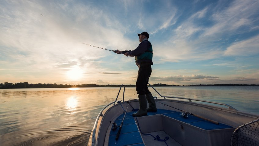 Portrait of a 65 year old  fisherman casting out his  fishing line into the water from his boat into a flat calm sea.