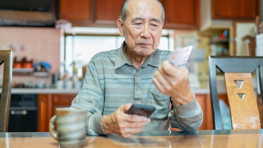 A senior man is shopping online on a smart phone.