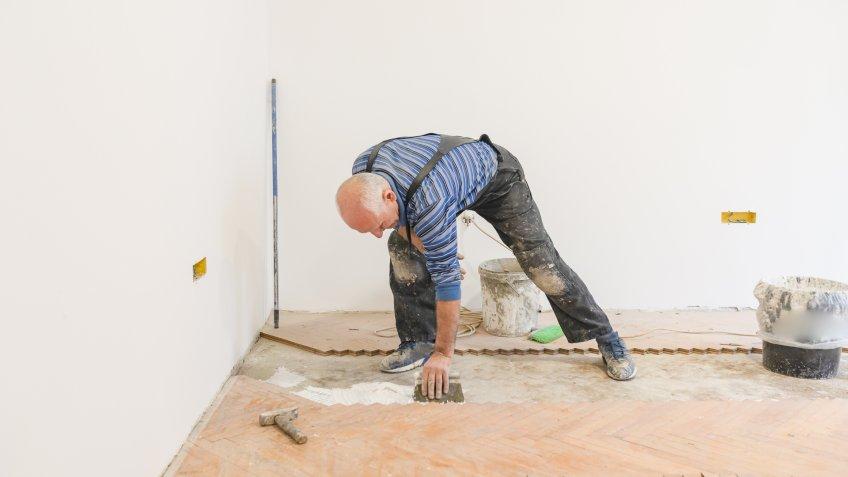 Parquet Carpenter Worker is Adding Glue on Base During Indoor Wood Flooring.