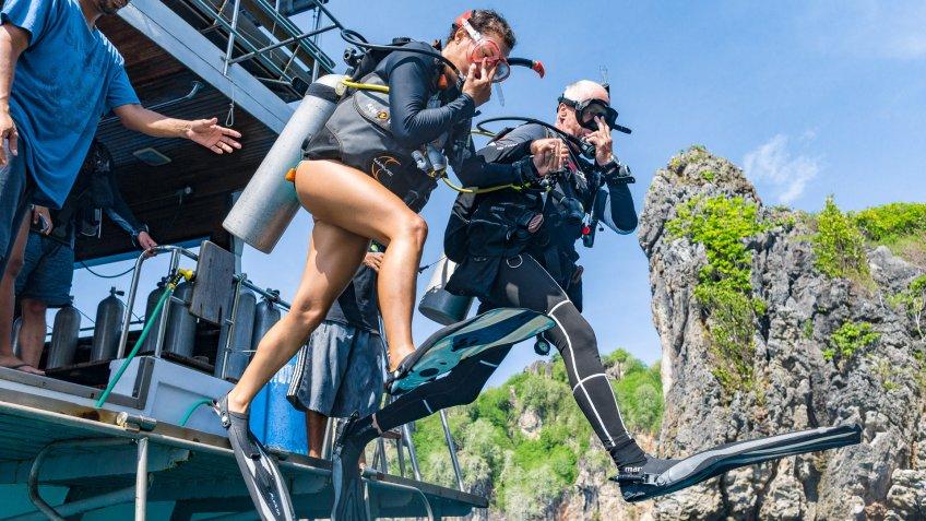 Bida Nai, Phi Phi Islands, Andaman sea, Thailand - May 24 2019: One young Woman and one senior man leap off a boat into the Andaman sea.
