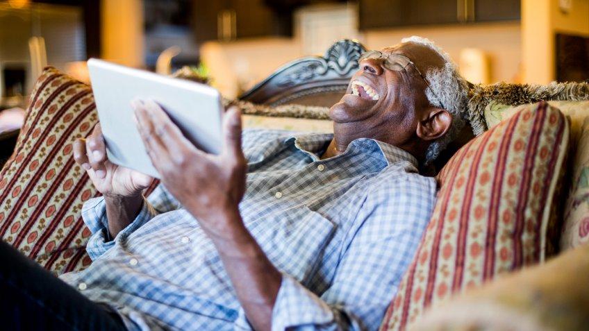 A senior black man streams content on a tablet.