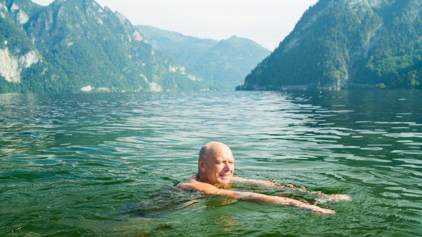 happy smiling active senior man enjoying refreshing swim in mountain lake in austria.