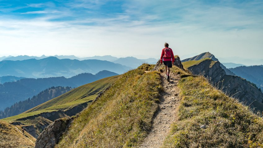 nice senior woman, hiking in fall, autumn  on the ridge of the Nagelfluh chain near Oberstaufen, Allgaeu Area, Bavaria, Germany, Hochgrats summit in the background.