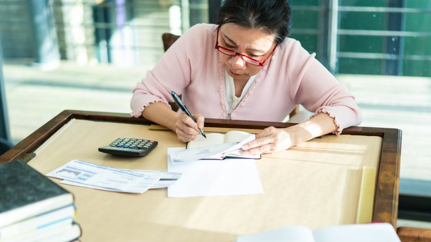 Taiwanese senior woman sitting at table, using calculator and writing results on paper.
