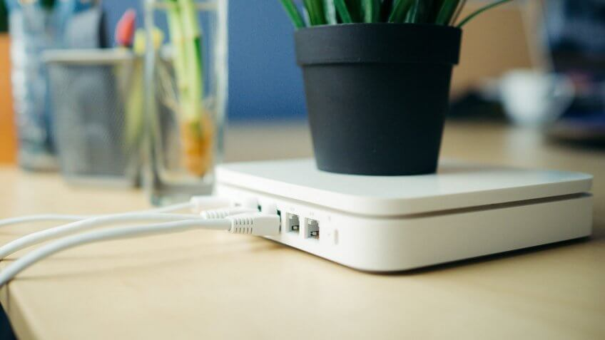 Closeup of a broadband router, plant in pot is placed on router, with a blur background.