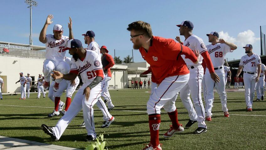Washington Nationals pitcher Sean Doolittle smashes a cabbage on a sidewalk while teammates cheer as part of a team building exercise and in recognition of National Cabbage Day during spring training baseball practice, in West Palm Beach, FlaNationals Spring Baseball, West Palm Beach, USA - 17 Feb 2020.