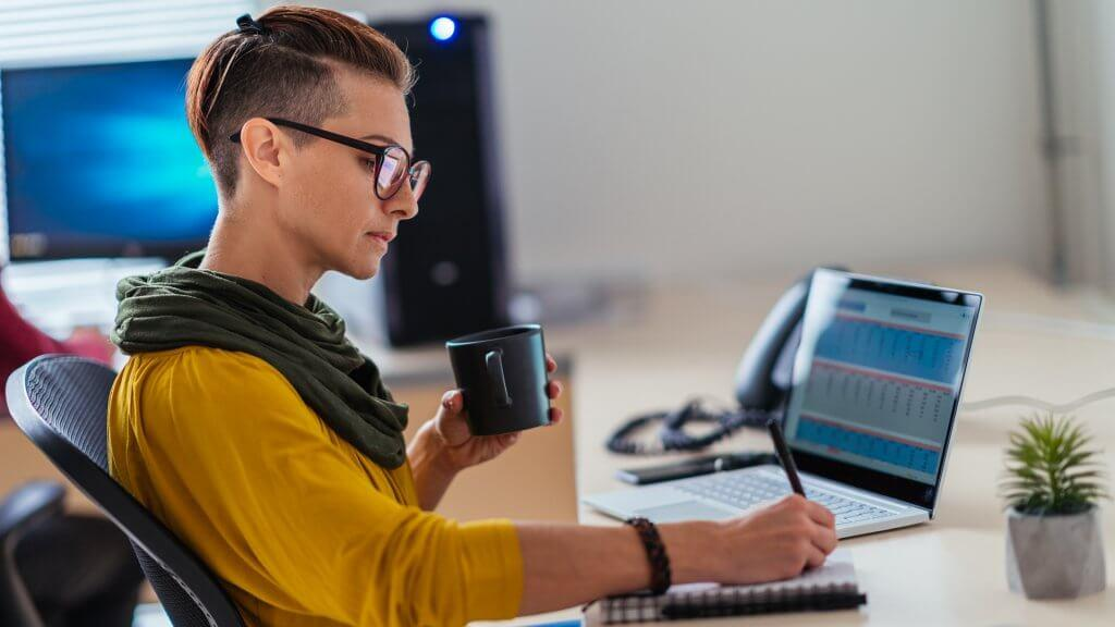 Businesswoman wearing yellow shirt writing notes in the office and drinking coffee.