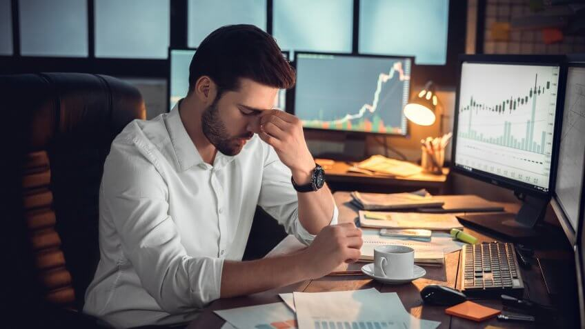 Depressed frustrated trader tired of overwork or stressed by bankruptcy, sad shocked investor desperate about financial crisis or money loss, upset businessman having headache massaging nose bridge.